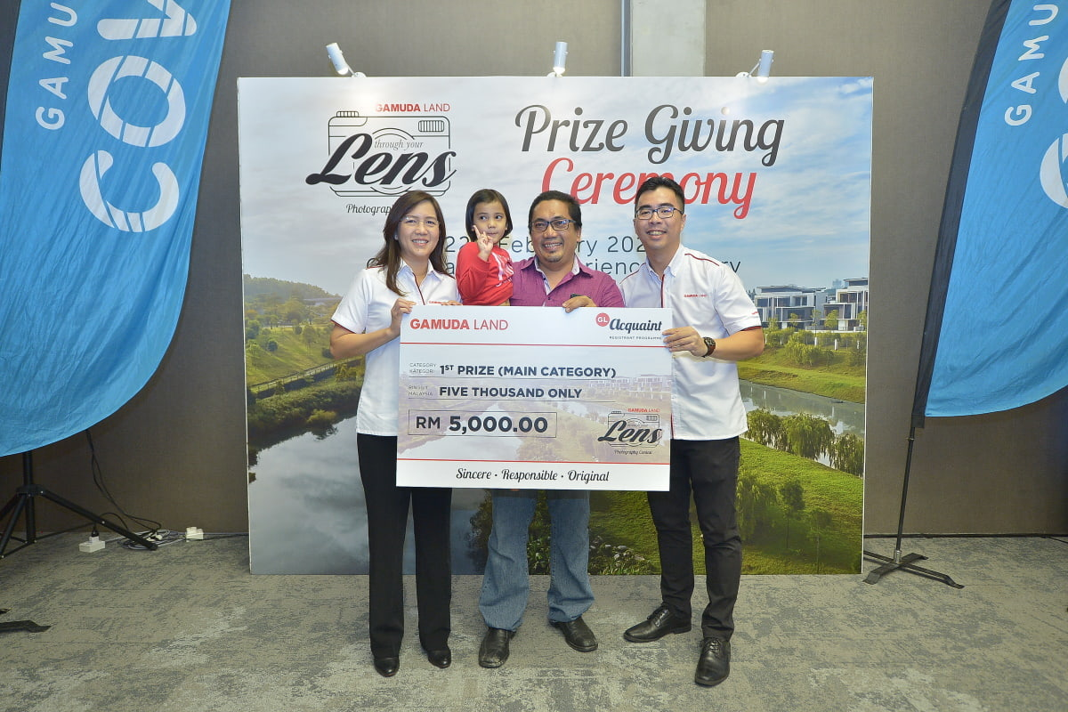 Proud moment: The first prize winner of Gamuda Land's 'Through Your Lens' January photography contest, Abdul Hafiz Ab Hamid (centre), is flanked by Aw (right) and marketing and sales executive director Lillian Lung at the Gamuda Cove township in Dengkil, Selangor.