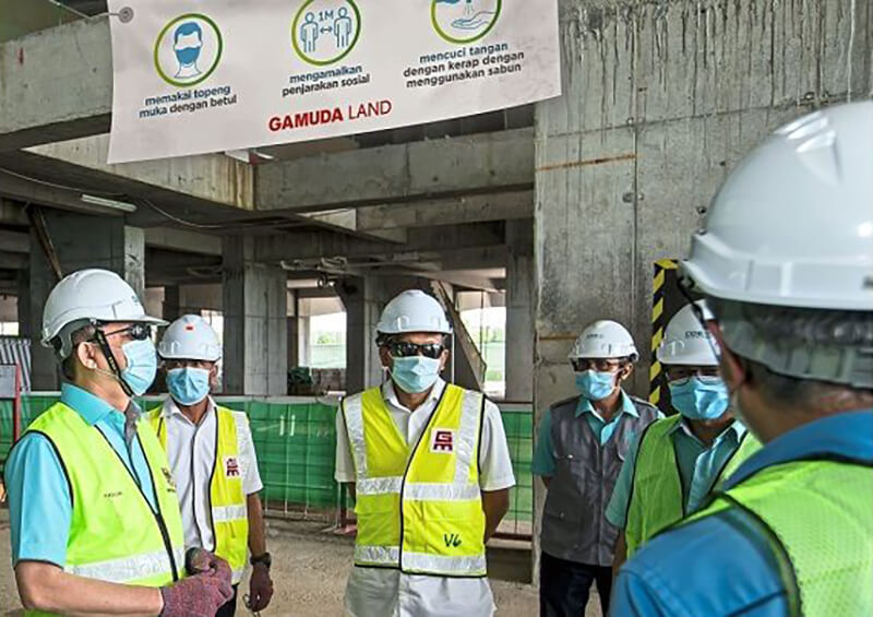 Fadillah (left) being briefed on the various precautionary measures taken against Covid-19 at Gamuda Land's twentyfive.7's construction site.